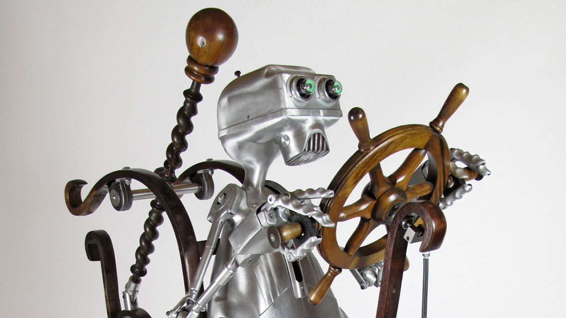 Kinetic sculpture of robot pedaling a wooden bicycle type machine.